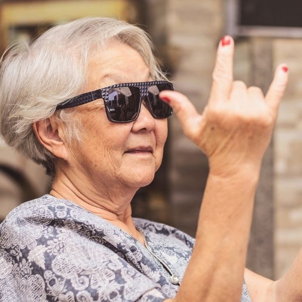 older asian woman making an i love you sign